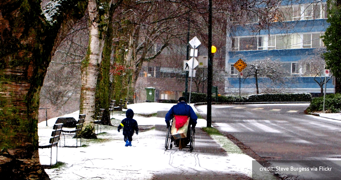 child walking with man in wheelchair on sidewalk in the snow - credit: Steve Burgess via Flickr